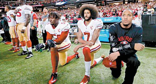 미국프로풋볼 선수들이 국가 연주 때 일어서지 않고 무릎을 꿇은 모습. [중앙포토]