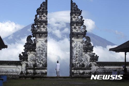 【발리(인도네시아)=AP/뉴시스】인도네시아 발리의 카랑가셈 사원에서 26일 한 남성이 구름으로 뒤덮힌 아궁 화산을 바라보고 있다. 아궁 화산의 폭발이 임박했다는 공포가 확산되는 가운데 인도네시아 당국은 이날 아궁 화산의 활동이 치명적 단계에 접어들었다고 말했다. 화산 폭발에 대한 우려로 약 7만5000명의 주민들이 대피했으며 관광객들도 화산 폭발 시 공항이 폐쇄될 것을 우려해 발리 체류 기간을 줄이기 시작했다. 2017.09.26