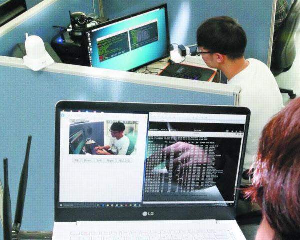 지난달 28일 서울 성북구 고려대 안암캠퍼스 산학관에 있는 보안 전문 업체 '노르마' 사무실에서 노르마 관계자가 CCTV 카메라를 해킹해보이고 있다. 해커 역할을 맡은 직원(아래쪽)이 해킹 프로그램을 이용해 피해자(위쪽) 컴퓨터 모니터 위에 설치된 카메라의 '맥(MAC) 주소'를 알아내고, 카메라에 접속해 영상을 빼냈다. 해킹 성공까지는 3분도 걸리지 않았다./김연정 객원기자