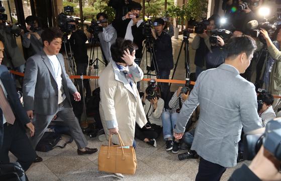 서 씨(가운데)가 12일 오후 서울경찰청 로비에서 몰린 기자들을 지나 조사실로 향하고 있다.