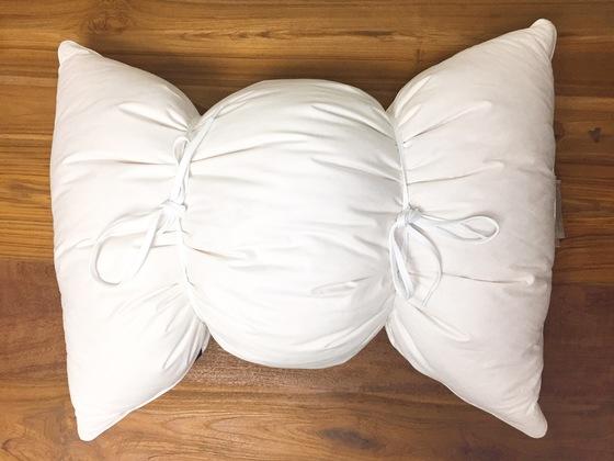 흰 운동화 끈으로 삼등분해 묶은 베개. 이 상태로 세탁기에 넣으면 된다.