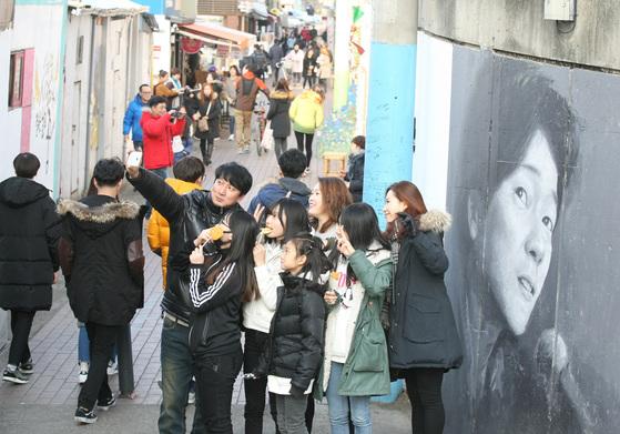 김광석 20주기이던 지난해 대구시 중구 방천시장 김광석길을 찾은 시민들이 김광석 벽화 앞에서 그의 음악을 들으며 기념 사진을 찍고 있다. 이제 대중에게 김광석은 어떤 이름으로 기억될까. [프리랜서 공정식]