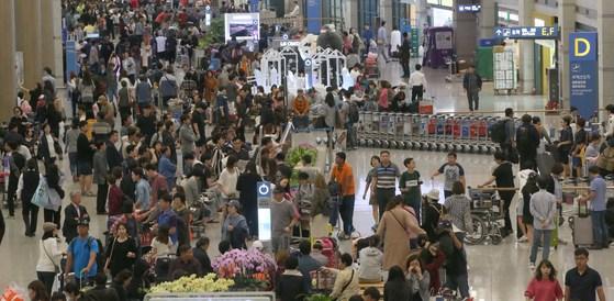 추석연휴 8일 오후 입국한 여행객들이 공항 청사를 가득 메웠다. 한 조사에 따르면 10일 이상 쉬는 기업은 300인 이상의 경우 88.6%인 반면, 300인 미만의 경우엔 56.2%에 그쳤다. [중앙포토]