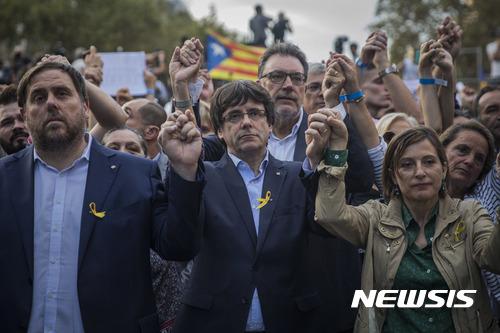 【바르셀로나=AP/뉴시스】21일(현지시간) 스페인 바르셀로나에서 카를레스 푸지데몬 카탈루냐 자치정부 수반(가운데)과 정부 관료들이 참가한 가운데 카탈루냐 분리독립 찬성 시위가 진행되고 있다. 2017.10.22.