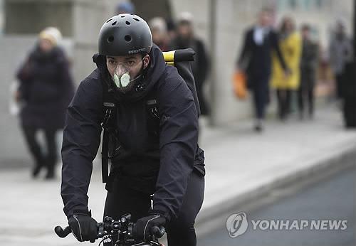 (런던 EPA=연합뉴스) 영국 런던의 대기오염이 중국 베이징보다 심한 가운데 한 자전거 이용자가 26일(현지시간) 마스크를 착용하고 있다.  2016475@yna.co.kr