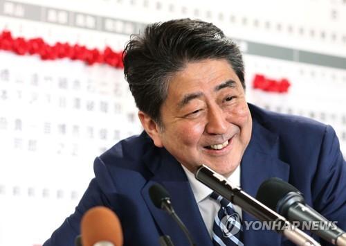(도쿄 교도=연합뉴스) 아베 신조(安倍晋三) 일본 총리가 지난 22일 총선 후 당 본부에 마련된 개표 상황실에서 방송사들과 인터뷰하며 활짝 웃고 있다.      choinal@yna.co.kr