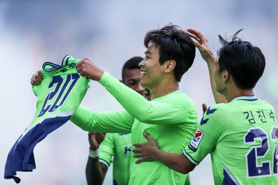 """이동국은 29일 관중석을 향해 자신의 유니폼의 이름을 펼쳐보이는 세리머니를 했다. 스페인 바르셀로나 메시가 지난 4월 레알 마드리드전 득점 후 유니폼을 펼쳐든 세리머니와 비슷했다. 이동국은 '전북 입단 후 홈팬들이 열정적으로 지지해줘 이 자리에 있을 수 있었다. 홈팬들에게 제 이름을 다시 한번 보여주고 싶었다""""고 말했다. [사진 프로축구연맹]"""