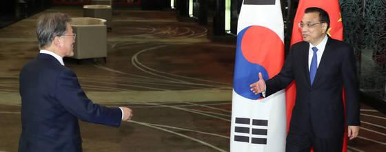 문재인 대통령이 13일 오후 '제31차 ASEAN 정상회의'가 열리는 필리핀 마닐라 소피텔 호텔에서 리커창 중국 총리와 회담장 앞에서 만나고 있다. [연합뉴스]