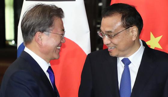문재인 대통령이 13일 오후 '제31차 ASEAN 정상회의'가 열리는 필리핀 마닐라 소피텔 호텔에서 리커창 중국 총리와 회담장 앞에서 만나고 있다.[연합뉴스]