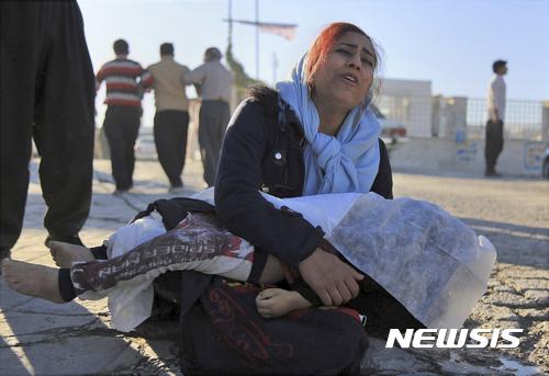 【사르폴에자합=AP/뉴시스】 이란 지진 피해가 가장 심한 서부 국경마을에서 13일 한 어머니가 딸 시신을 안고 애통해하고 있다. 2017. 11. 13.