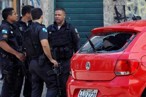 경찰이 무장괴한들에게 강도를 당한 차량을 조사하고 있다. [브라질 일간지 에스타두 지 상파울루]