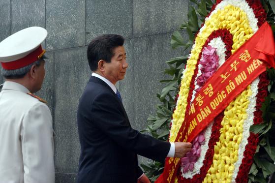 베트남을 국빈방문 중인 노무현 전 대통령이 호치민 묘소를 방문, 영예수행장관(왼쪽)의 안내를 받으며 헌화하고 있다. [중앙포토]