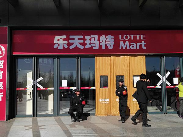 ⓒReuter 지난 3월14일, 영업 정지된 롯데마트 점포 앞을 지키던 중국 공안이 지나가는 사람의 질문에 대답하고 있다.