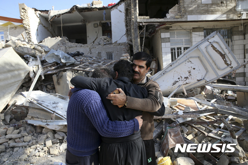 【사르폴 에 자하브=AP/뉴시스】 이란 일가족이 15일(현지시간) 서부 사르폴 에 자하브에서 무너진 주택 앞에서 서로 안고 슬퍼하고 있다. 2017.11.17