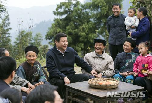 【화위안(중 후난성)=AP/뉴시스】시진핑(習近平) 중국 국가주석이 지난 2013년 11월3일 중국 후난(湖南)성 샹시투자-먀오족 자치주의 후위안(花垣)에서 마을 주민들과 이야기하고 있다. 지금 중국에선 시진핑에 대한 신격화가 마오쩌둥(毛澤東) 이후 최대 규모로 벌어지고 있다. 일부에서는 개인 우상화는 과거의 아픈 기억을 되살린다며 중국에 결국 화가 될 것이라고 얘기하고 있다. 2017.11.22