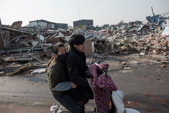 중국 베이징시에서 농민공으로 보이는 젊은 남녀가 오토바이를 타고 최근 대규모 빈민촌 정리 작업으로 폐허가 된 거주지를 지나가고 있다. /베이징=AFP연합뉴스