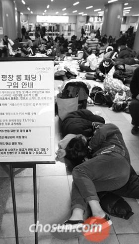 지난 11월 '평창 롱패딩'을 사기 위해 일부는 누워서, 일부는 뜬 눈으로 밤샘 줄을 이룬 사람들./조인원 기자