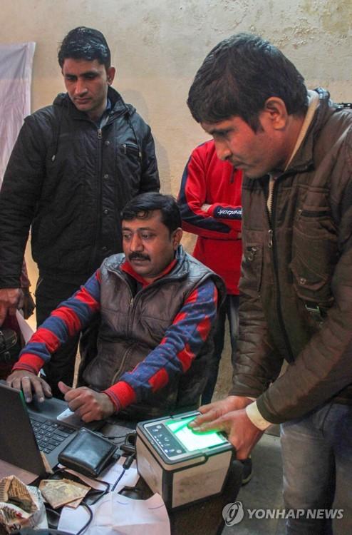 6일 인도 북부 하리아나 주 구루그람에 있는 고유식별청(UIDAI) 사무실에서 한 남성이 아다르 번호 신청을 위해 지문을 등록하고 있다.[연합뉴스 자료사진]