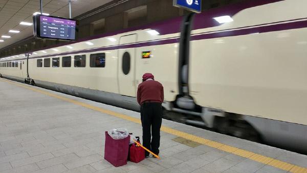 SRT 열차가 수서역에 진입하자 고개 숙여 인사하는 청소노동자. 경향신문 독자 박준규씨 제공