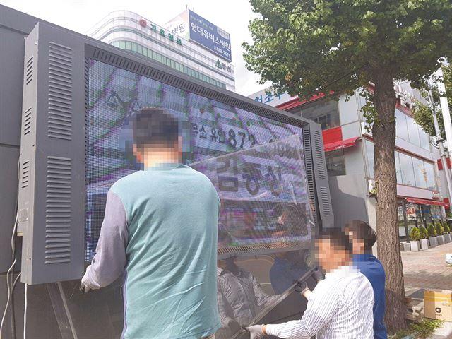 김용훈(왼쪽 두 번째)씨가 재활공동체 관계자들과 버스정류장 영상광고판 교체 작업을 하고 있다. 박재현 기자