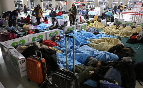 제주공항 이용객들이 지난 12일 공항 바닥에 깔린 매트리스 위에서 자거나 쉬고 있다. [연합뉴스]