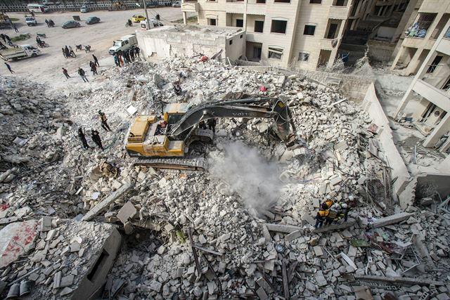 5일 시리아 정부군과 러시아군의 공습으로 폐허가 된 시리아 이들리브시에서 민간구조대, 이른바 '하얀 헬멧' 대원들이 중장비를 이용해 부서진 건물 잔해를 치우며 생존자 구조 작업을 벌이고 있다. 이들리브=EPA 연합뉴스