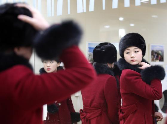 북한 응원단이 7일 오후 강원도 인제로 이동하던 중 가평휴게소에 도착해 휴식을 취했다. 응원단원들이 화장실에서 거울을 보며 모자 등을 단장하고 있다.[연합뉴스]