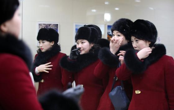 북한 응원단이 7일 오후 강원도 인제로 이동하던 중 가평휴게소에 도착해 휴식 시간을 가졌다. 여성 응원단원들이 화장실에서 거울을 보며 옷매무시를 가다듬고 있다.[연합뉴스]
