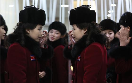 북한 응원단이 7일 오후 강원도 인제로 이동하던 중 가평휴게소에 도착해 휴식 시간을 가졌다. 한 여성 응원단원이 화장실에서 거울을 보며 화장을 고치고 있다. [연합뉴스]