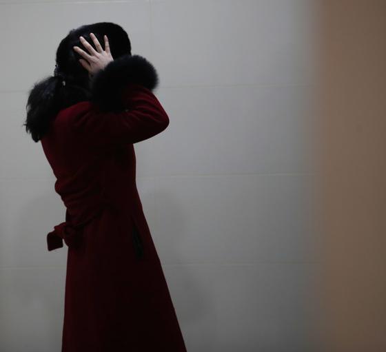 북한 응원단이 7일 오후 강원도 인제로 이동하던 중 가평휴게소에 도착해 휴식 시간을 가졌다. 한 여성 응원단원이 화장실에서 거울을 보며 모자를 고쳐 쓰고 있다.[연합뉴스]