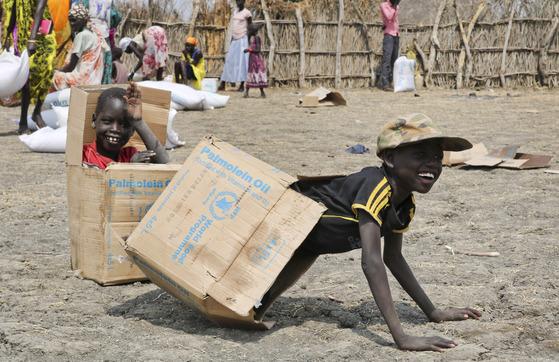 지난달 20일(현지시간) 남수단 아코보 타운에서 구호단체 옥스팜이 식량을 지급하고 남은 빈 박스를 장난감 삼아 가지고 노는 아이들. [AP=연합뉴스]