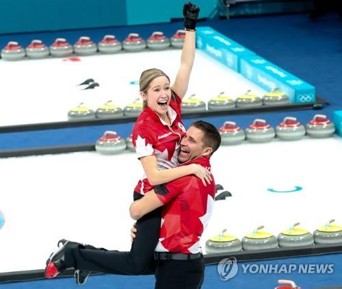 올림픽 최초의 믹스더블(혼성 2인조) 컬링 금메달리스트가 된 캐나다의 케이틀린 로스(왼쪽)와 존 모리스가 기쁨을 나누는 모습. [EPA=연합뉴스]