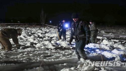 【 AP/뉴시스】러시아 도모데도보 공항으로부터 약 40km 떨어진 스테파노프스코예 마일에서 11일(현지시간) 긴급상황부 소속 직원들이 안토노프(An)-148 여객기 추락현장을 조사하고 있다. 이 사고로 탑승객 71명은 전원 사망한 것으로 보인다. 사진은 러시아 긴급상황부가 제공한 것이다. 2018.2.12