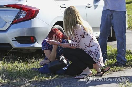 주저앉은 사람을 위로하는 여성[AP=연합뉴스]