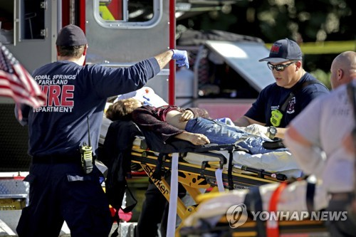 지난 14일(현지시간) 미국 플로리다 주 파크랜드에 위치한 마조리 스톤맨 더글러스 고교에서 총기 난사 사건이 벌어져 병원으로 이송되고 있는 피해자 [AP=연합뉴스]