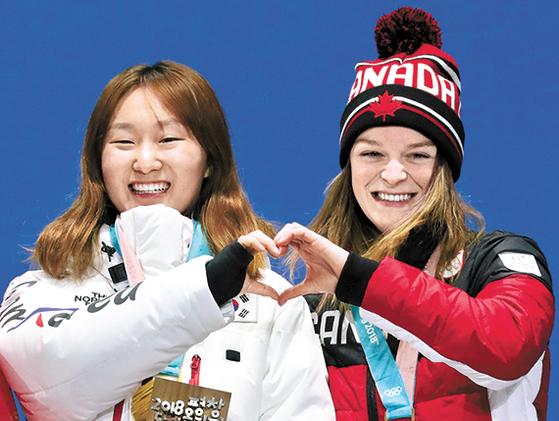 1500m에서 금메달 을 딴 최민정이 동메달리스트 킴 부탱(캐나다)과 하트 세리머니를 하는 모습. [우상조 기자]
