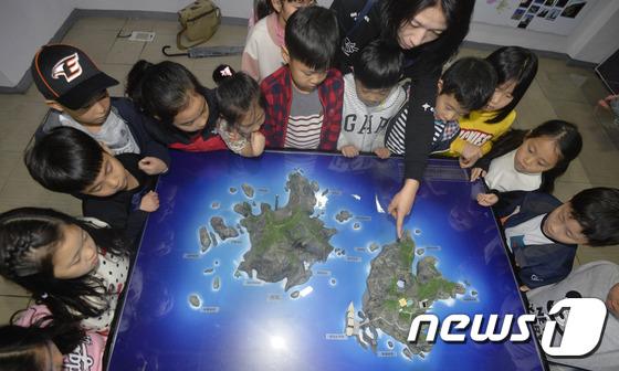 독도 모형 전시관을 찾은 초등학교 학생들이 선생님에게 독도에 관한 설명을 듣는 모습. (뉴스1DB) © News1 주기철 기자