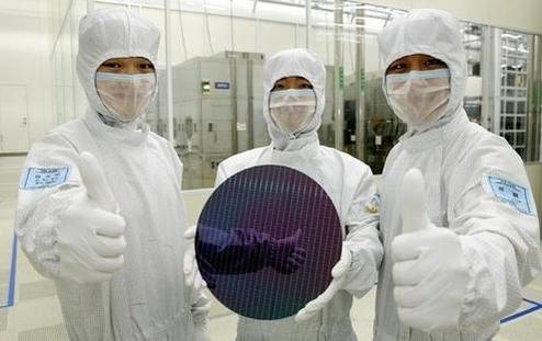 삼성전자 반도체 부문 직원들이 생산된 실리콘 웨이퍼를 들고 포즈를 취하고 있다. / 삼성전자 제공