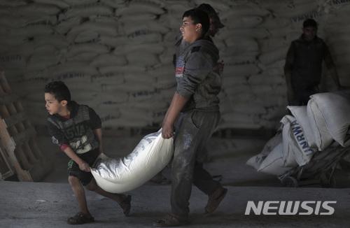 【샤티난민수용소(가자지구)= AP/뉴시스】 14일 팔레스타인 가자시티의 샤티 난민수용소에 있는 유엔 창고에서 구호식량을 배급받은 팔레스타인 사람들이 밀가루 포대를 집으로 옮겨가고 있다. 2018.1.16
