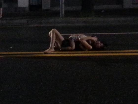 아동학대 혐의로 검찰에 송치된 A목사가 2014년 6월 전북 전주시 중앙동 4차선 도로 중앙선 부근에서 자신이 입양한 남자아이(당시 3세)를 품에 안은 채 드러누워 괴성을 지르고 있다. [사진 동영상 캡처]