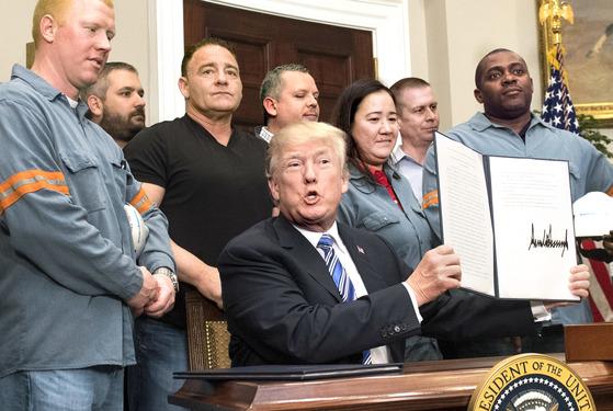 도널드 트럼프 미국 대통령이 지난 8일(현지시간) 백악관 루스벨트룸에서 철강 노동자들이 지켜보는 가운데 외국산 철강 및 알루미늄 제품에 고관세를 부과하는 행정명령에 서명한 뒤 들어보이고 있다. [UPI]