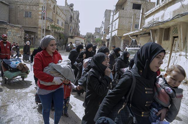 시리아 동구타 지역에 거주하던 주민들이 24일 정부군과 반군의 합의로 설정된 안전지대를 통해 동구타에서 탈출하고 있다. 다마스쿠스=EPA 연합뉴스