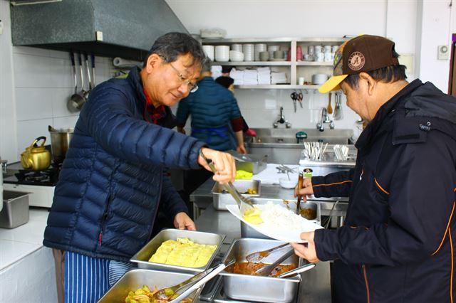 서영남(왼쪽) 민들레국수집 대표가 지난 26일 식당을 찾은 한 노숙자에게 직접 배식을 하고 있다.