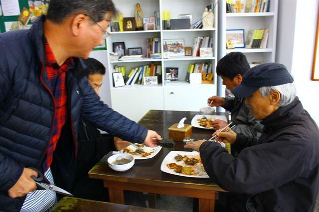 서영남(왼쪽 첫번째) 민들레국수집 대표가 지난 26일 식사 중인 한 노숙자에게 직접 김을 얹어 주고 있다.
