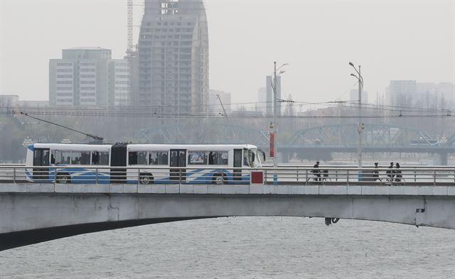 평양 옥류관에서 바라본 대동강 다리위에 전차가 지나가고 있다.