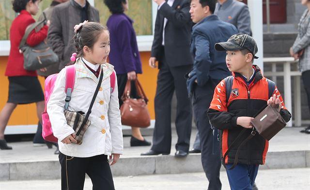 개학을 맞아 학교에 다녀오는 학생들. 교복 위에 사복 외투를 입었다.