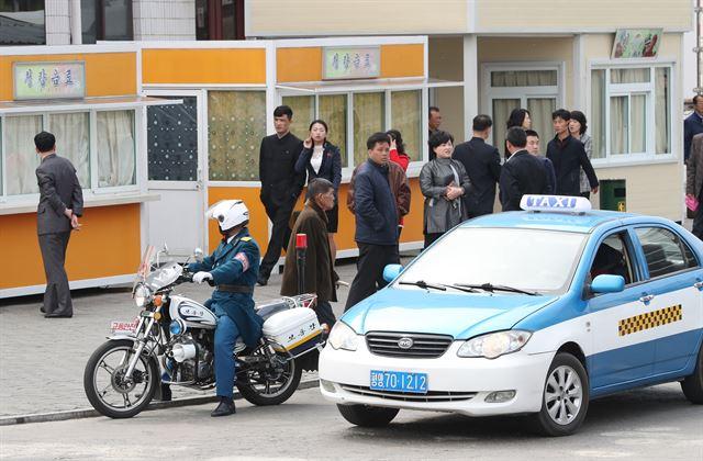 평양 창전거리에서 교통경찰 오토바이와 택시가 신호 대기를 하고 있다.