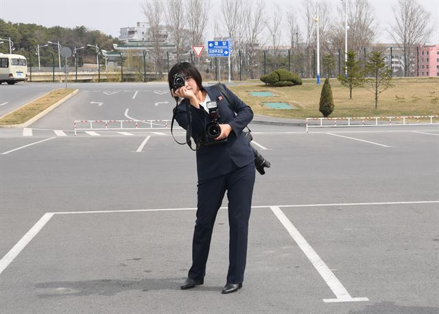 남측 기자단의 평양순안공항 도착 기념사진을 찍어주고 있는 북측 로금순 조선신보 기자.