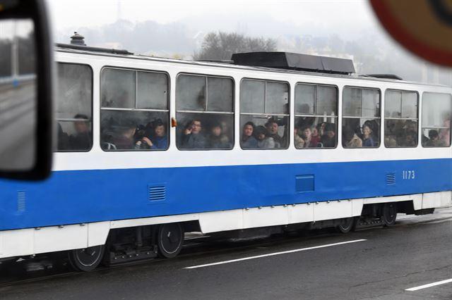 전차에 탑승한 시민들이 공연단이 지나가는 모습을 호기심 어린 눈으로 보고 있다.