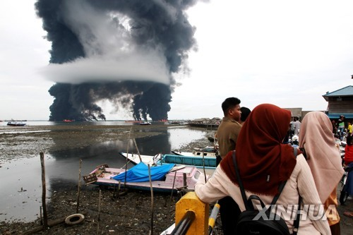 2018년 3월 31일 인도네시아 동(東) 칼리만탄 주의 주도인 발릭파판 앞바다에서 유출된 원유에 불이 붙으면서 검은 연기가 치솟고 있다. [신화=연합뉴스]